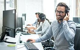 Un téléconseiller souriant devant son écran et en ligne